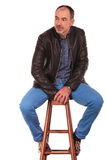 Mature man in leather jacket posing seated Stock Photo