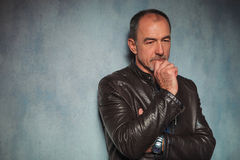 Mature man in leather jacket standing and thinking Royalty Free Stock Image
