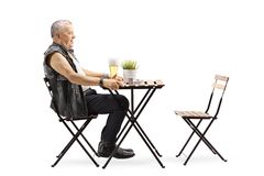 Mature man in a leather vest sitting at a table with a glass of beer stock photography