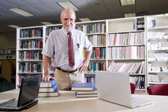 Mature man at library table with textbooks. Portrait of mature man at library table with textbooks, professor researching Royalty Free Stock Photos