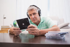 Mature man listening to cds. At home in the living room royalty free stock images