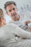 Mature man listening to his wife and drinking coffee Royalty Free Stock Image
