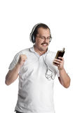 Mature man listening to music on headphones Stock Images