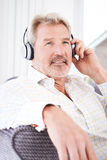 Mature Man Listening To Music On Wireless Headphones Royalty Free Stock Photo