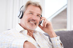 Mature Man Listening To Music On Wireless Headphones Royalty Free Stock Images