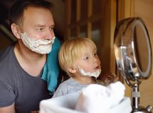 Mature man and little boy having fun with foam during shaving together. Kid son imitates his father royalty free stock photo