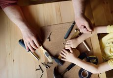 Mature man and little boy make a wooden toy together. Father learn his son work with tools.Traditional education of boy. Family`s royalty free stock image