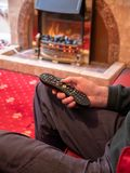 Elderly man living alone, with tv remote control in hand stock image