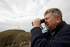 Mature man looking through binoculars Royalty Free Stock Images