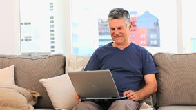 Mature man looking at  his laptop stock footage