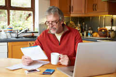 Mature Man Looking At Home Finances In Kitchen Royalty Free Stock Image