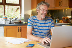 Mature Man Looking At Home Finances In Kitchen Stock Photos