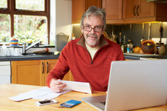 Mature Man Looking At Home Finances In Kitchen Royalty Free Stock Photos