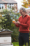 Mature Man Looking At Honey Produced By His Own Bees. Smiling Royalty Free Stock Image