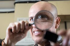 Mature man looking through a magnifying glass on a item Royalty Free Stock Photography