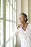 Mature man looking out a large window. Stock Photos