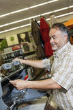 Mature man looking at price tag of machinery in hardware store Royalty Free Stock Photography