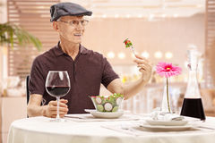Mature man looking at a salad in disgust Stock Images