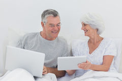 Mature man looking at wifes tablet pc Stock Image