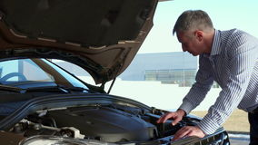 Mature man looks at the car engine at the dealership stock video