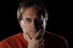 Mature man looks quizzical on black background Royalty Free Stock Photos