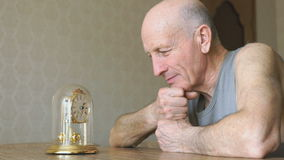 Mature man looks at the table clock with pendulum stock footage