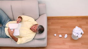 Mature man lying on couch writing ideas and tossing them stock video