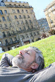 Mature man lying in grass in citytown. Mature man having a nap in city park Royalty Free Stock Photography