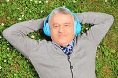 Mature man lying on grass with headphones, listening to music stock photography