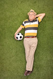Mature man lying on grass and holding a soccer ball Stock Image