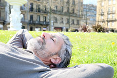 Mature man lying in grass in public park. Mature man having a nap in city park Royalty Free Stock Image