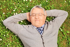 Mature man lying on green grass Royalty Free Stock Photography