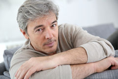 Mature man lying on sofa. Portrait of mature man relaxing at home in sofa stock photo
