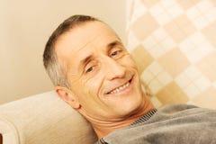 Mature man lying on the sofa Stock Photo