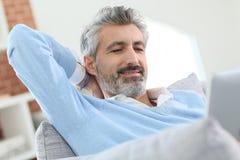Mature man lying on sofa websurfing on tablet Stock Photos