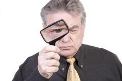 Mature Man with Magnifying Glass Royalty Free Stock Images