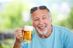 Mature man make cheers with beer. Mature man make cheers with a glass of beer Stock Photos