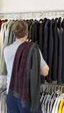 Mature man making decision of which sweater to wear. Vertical portrait of mature man in walk-in closet over looking his sweaters for wearing Royalty Free Stock Images