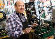 Mature man making duplicates of keys. Joyful smiling mature man in apron working in locksmith and making duplicates of keys stock images