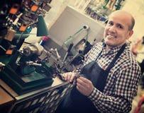 Mature man making duplicates of keys Royalty Free Stock Images