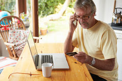 Mature Man Making On Line Purchase Using Credit Card Royalty Free Stock Photos