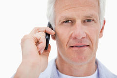 Mature man making a phone call. Against a white background Royalty Free Stock Photography