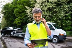 Mature man making a phone call after a car accident. Copy space. Stock Photography