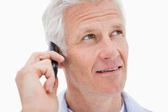 Mature man making a phone call while looking up. Against a white background royalty free stock photography