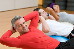 Mature man making sit-ups. Healthy people with mature instructor doing sit-ups at gym Royalty Free Stock Photos