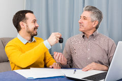 Mature man and manager contract car lease. Adult men and manager signed contract car hire at home and hand over keys stock image