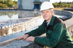 Mature man manual worker. In white hardhat near sewage treatmant basin stock photos