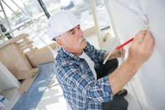 Mature man marking wall with pencil Stock Image