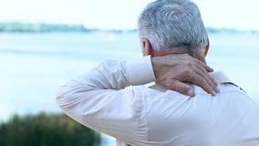 Mature man massaging neck and shoulders, aging health problem, painful injury royalty free stock photo