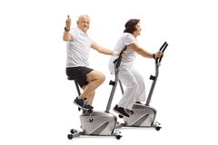 Mature man and a mature woman on exercise bikes with the man mak Royalty Free Stock Photography